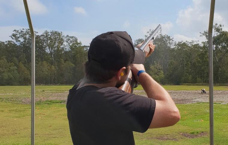 man shooting shotgun with black cap