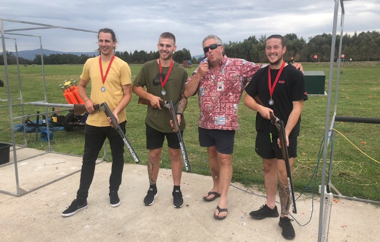 group of people smiling in casual clothing outside holding guns