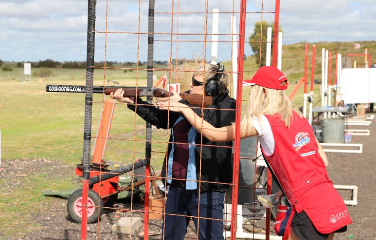 two people holding gun pointing at target