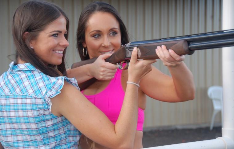 two women smiling holding gun